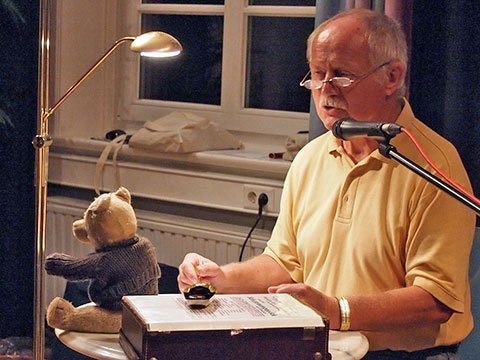 Joachim Grabbe bringt zu seiner Lesung aus Kinnerdag in Neendörp authentisches Zubehör mit: Der kleine Bereitschaftskoffer und der geliebte Teddy mussten bei Fliegeralarm  mit in den Keller