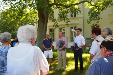 Herwyn Ehlers (m) und Dr. Sebastian Dorsch (r) erklärten das Gebäude und die Parkanlage.